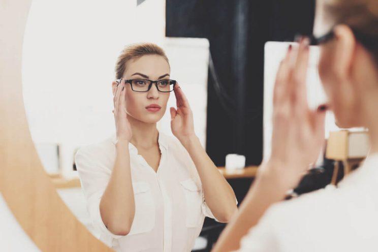Woman adjusting glasses