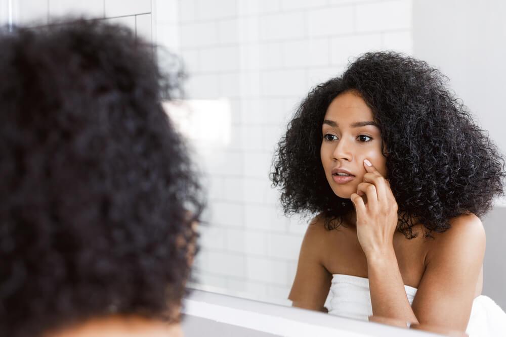 Woman looking at skin in mirror - bad facial