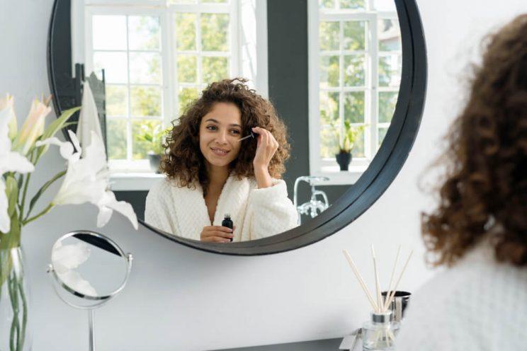Woman applying eye serum