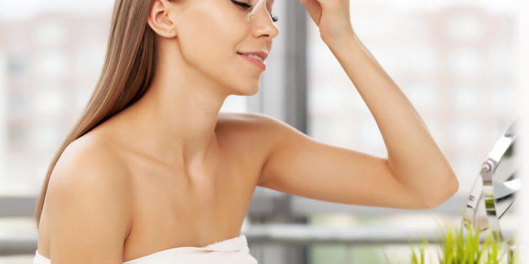 Woman applying skin serum